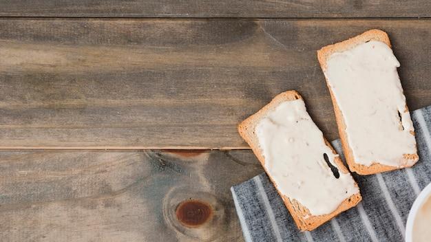 Pão torrada com queijo espalhado na mesa de madeira