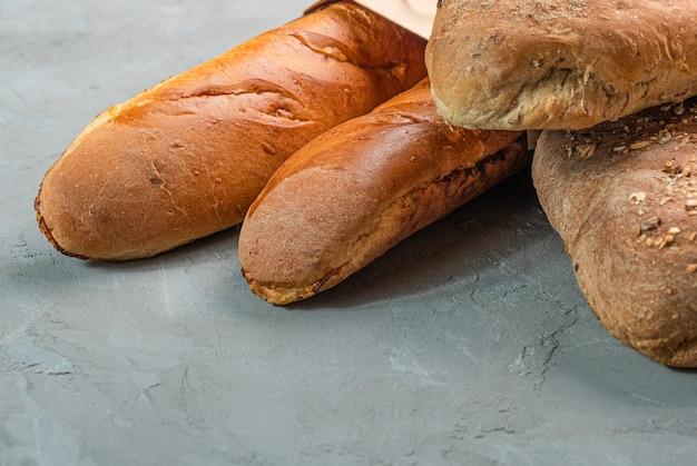 Pão torrado caseiro fresco e close-up de baguetes. conceito para banners, vista superior em um fundo cinza.