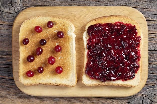 Pão torrado com geléia de cranberry e frutas vermelhas na mesa da cozinha