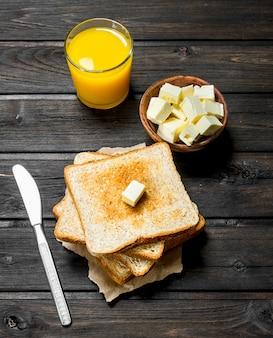 Pão torrado com manteiga e suco de laranja em mesa rústica