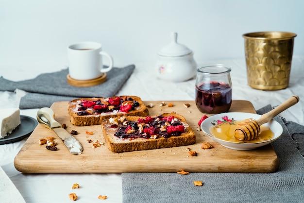 Pão torrado com mel, queijo creme, geléia de frutas vermelhas e café