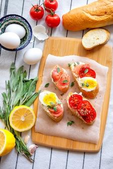 Pão torrado com mussarela, ovos e tomates.