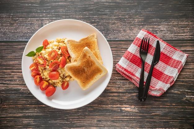 Pão torrado com ovos mexidos e tomate cereja em uma mesa de madeira e guardanapo vermelho