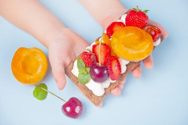 Pão torrado com queijo creme, frutas e bagas em uma mão de criança