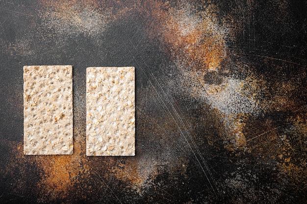 Pão torrado com sementes de girassol, chia e gergelim, em fundo de mesa rústica escura velha, vista de cima plana lay, com espaço de cópia para o texto