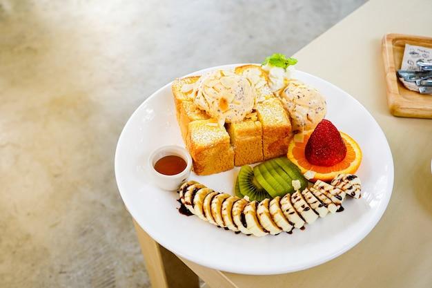 Pão torrado de mel servido com frutas mistas, banana fatiada, sorvete e coberto com rodela de amêndoa e calda de mel