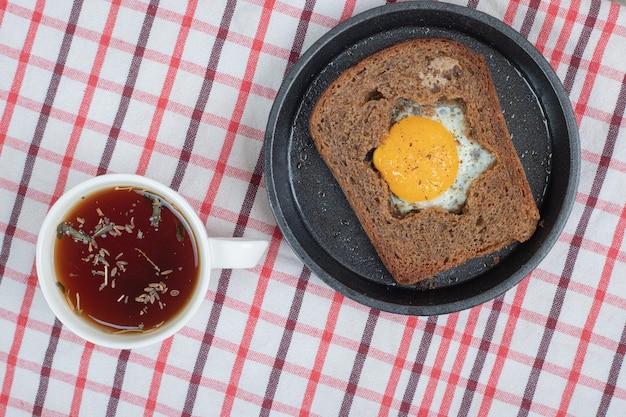 Pão torrado de ovo e xícara de chá na toalha de mesa. foto de alta qualidade