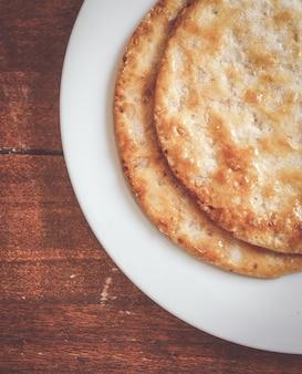 Pão torrado em um prato branco sobre uma superfície de madeira