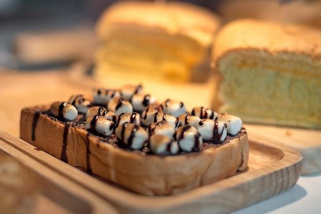 Pão torrado fatiado com cobertura de marshmello com calda de chocolate na placa de madeira