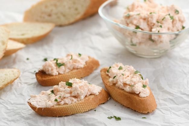 Pão torrado fatiado ungido patê de salmão com queijo macio e ervas no papel