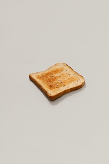 Pão torrado fresco em superfície cinza com luz do sol