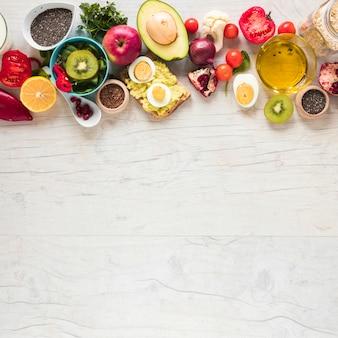 Pão torrado; frutas frescas; legumes e ingredientes dispostos na mesa