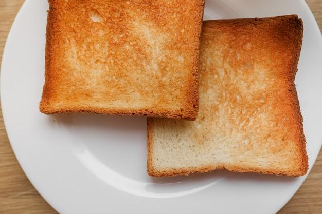 Pão torrado na hora. saboroso pão torrado na placa de madeira. um par de torradas crocantes em um close-up de placa. delicioso café da manhã