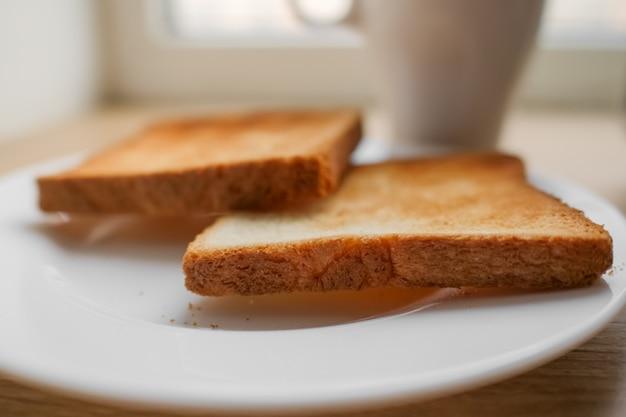Pão torrado na hora. saboroso pão torrado na placa de madeira. um par de torradas duras na torradeira, close-up. delicioso café da manhã