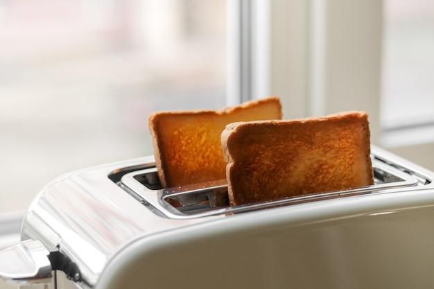 Pão torrado na hora. um par de torradas duras na torradeira, close-up. delicioso café da manhã. foco seletivo