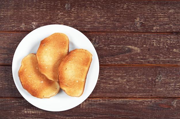 Pão torrado no prato na velha mesa de madeira