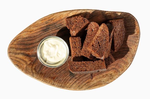 Pão torrado preto apetitoso com molho em uma placa de madeira.