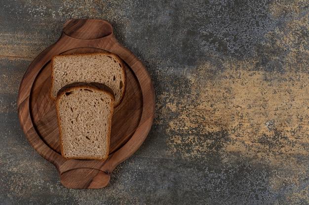 Pão torrado preto em prato de madeira