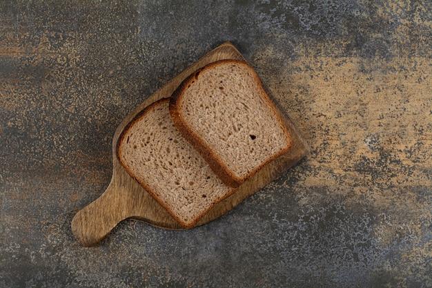 Pão torrado preto na placa de madeira.