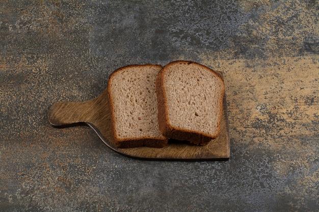Pão torrado preto na tábua de madeira