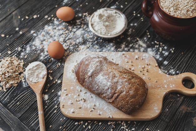 Pão tradicional fresco na mesa de madeira. fundo escuro temperamental com espaço de texto livre.