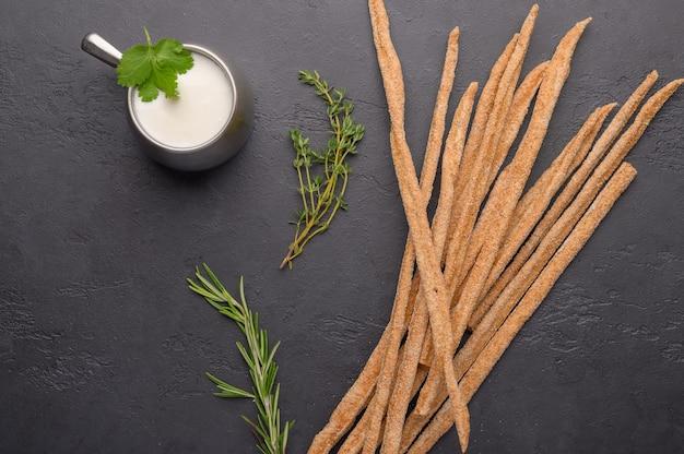 Pão tradicional italiano grissini com ervas e uma caneca com leite fermentado ayran em um fundo escuro.