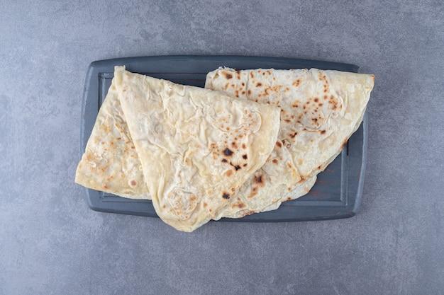 Pão tradicional lavash de trigo na bandeja de madeira, sobre o mármore.