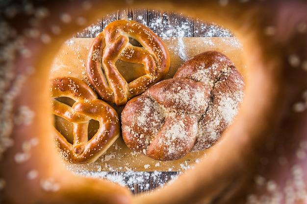 Pão trançado e pretzels na tábua de cortar vista através de bagels