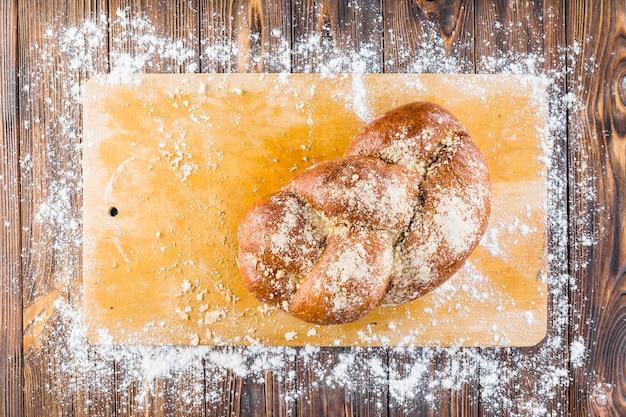 Pão trançado na tábua de cortar com farinha branca espalhada