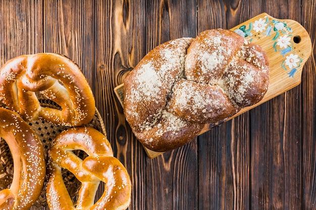 Pão trançado na tábua e pretzels na cesta sobre a mesa