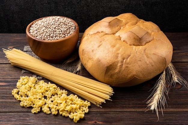 Pão, trigo e macarrão em fundo escuro de madeira
