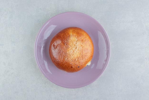 Pão único doce no prato roxo.