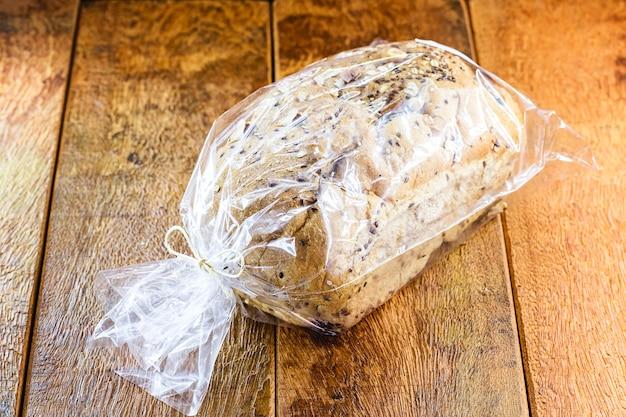 Pão vegano feito com grãos acondicionados em saco plástico, produto artesanal à venda