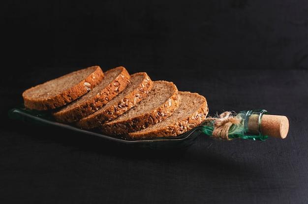 Pão wholegrain cortado com sementes de linho, sementes de girassol e sésamo em uma placa feita da garrafa no fundo preto.