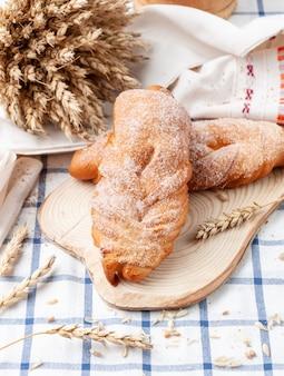 Pãozinho caseiro de vime polvilhado com açúcar. em uma placa de madeira. toalha de mesa branca com listras azuis. ao fundo, uma espiga de trigo e grãos. estilo sertanejo
