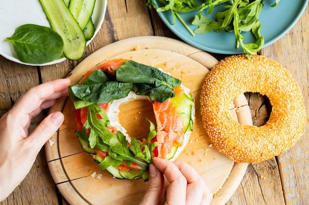 Pãozinho com salmão. menina está preparando um sanduíche no café da manhã.