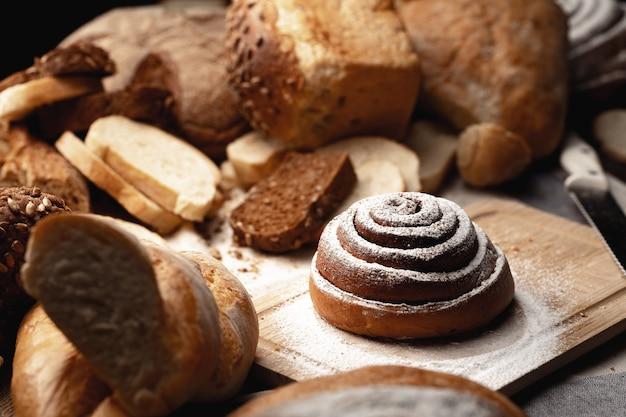 Pãozinho de canela fresca com açúcar em pó na placa de madeira