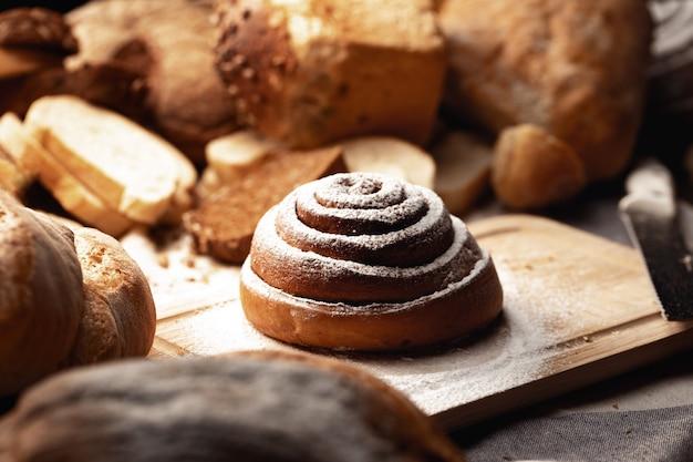 Pãozinho de canela fresco com açúcar em pó na placa de madeira