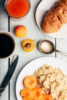Papa de aveia com alperce fatiado, xícara de café, copo de suco de toranja e croissant