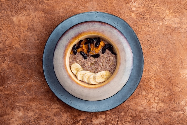 Papa de aveia do vegetariano do linho das sementes frescas com amêndoas e os abricós secados em um fundo claro. fonte omega 3.