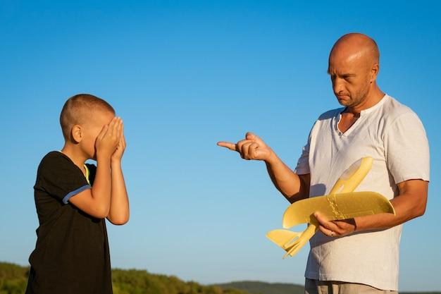 Papa repreende seu filho, por aquele brinquedo quebrado ao ar livre