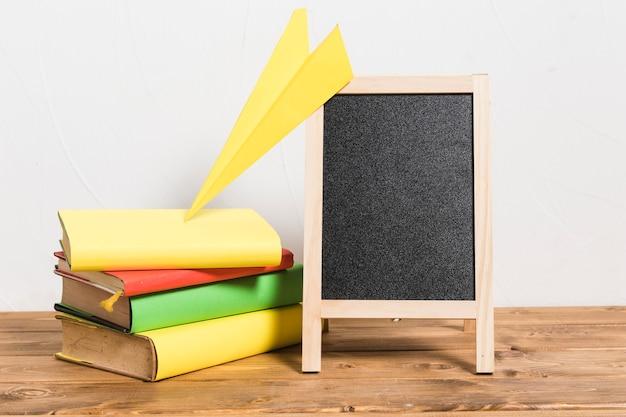 Papagaio de papel na pilha de livros antigos coloridos e quadro vazio na mesa de madeira