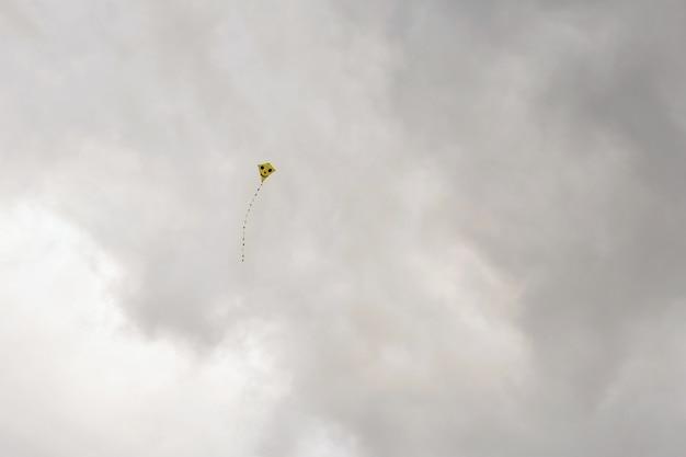 Papagaio que voa no dia ventoso bonito do outono. fundo do céu azul com sol e nuvens.