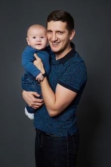 Papai abraça e beija seu filho pequeno. um homem segura uma criança nos braços