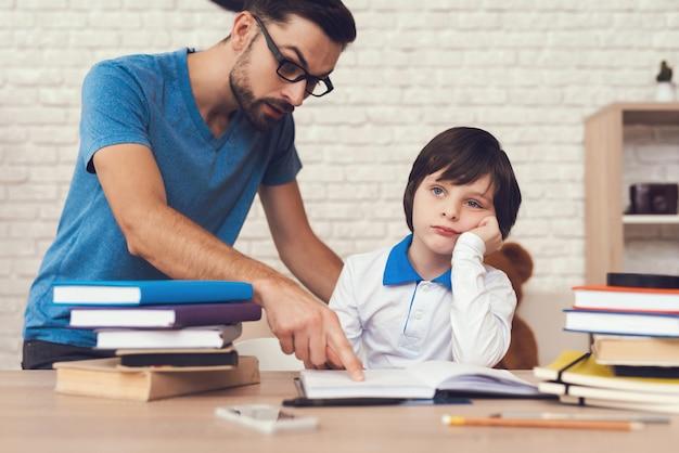 Papai ajuda o filho, e o filho fica entediado.