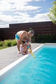 Papai ajudando a menina. papai ajudando sua linda garota usando uma pistola d'água perto da piscina