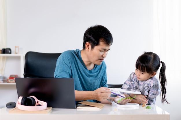 Papai asiático está ensinando sua filha a aprender sobre a textura e o formato das folhas através de lupa.
