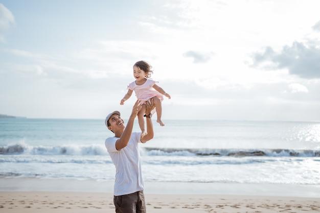 Papai balançando sua filha no ar na praia se divertindo juntos
