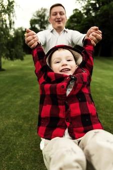 Papai brinca com o filho no parque. pai segura o filho pelas mãos e o rola. pai e filho estão se divertindo. uma família feliz. o jovem ri.