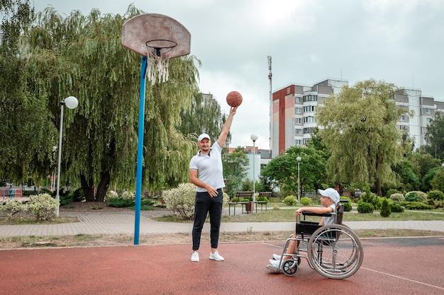 Papai brinca com seu filho deficiente no campo de esportes. cadeira de rodas conceito, pessoa com deficiência, vida plena, pai e filho, atividade, alegria, basquete.